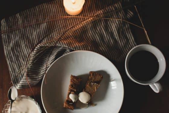 Kürbis Bananenbrot mit Frischkäsedip auf einem dunklen Holztisch mit einer Kerze. Herbstliches Ambiente