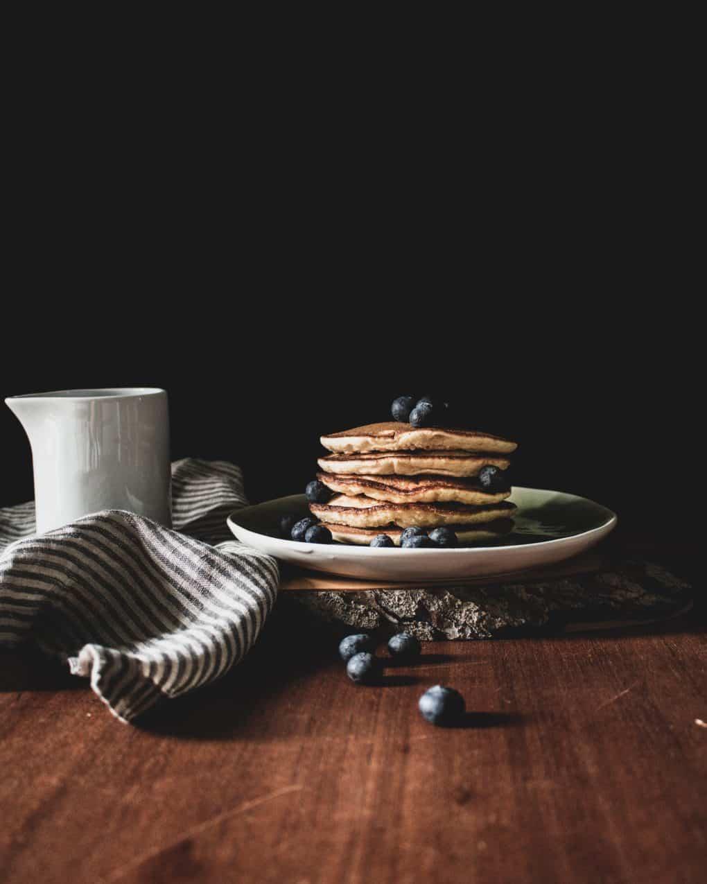 Pancakes gestapelt mit Ahornsirup und Blaubeeren
