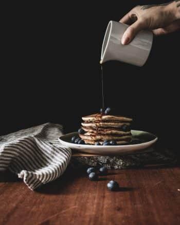 Pancakes gestapelt mit Blaubeeren und Ahornsirup