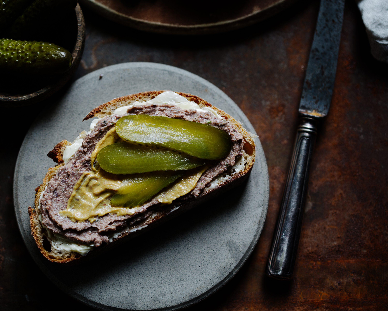 Vegane Leberwurst auf einem Stück Brot mit Gewürzgurke und Senf